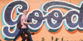 a man walking by wall mural