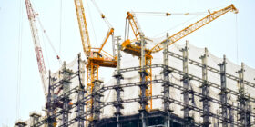 an upwards shot of two cranes on a building construction site