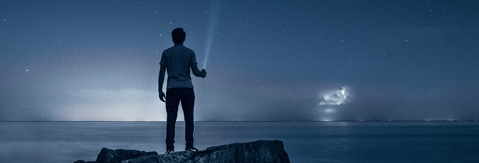a man standing on a rock at the beach at night