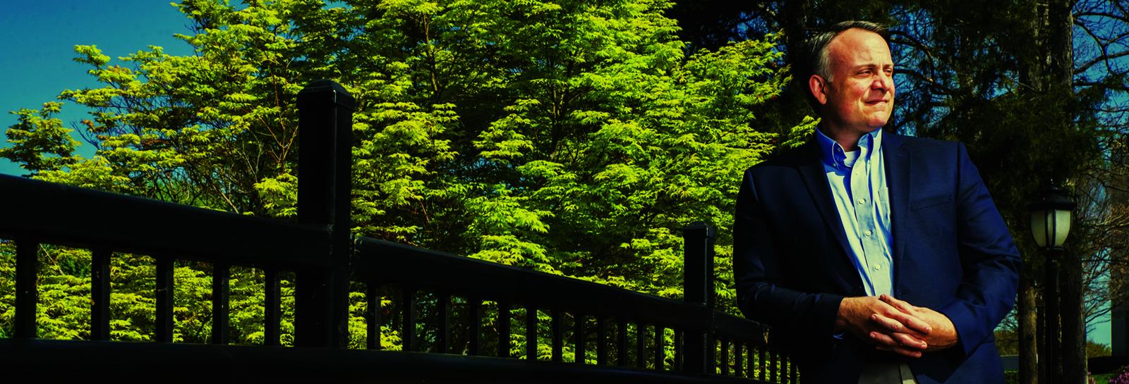 a man leaning on a railing of a bridge