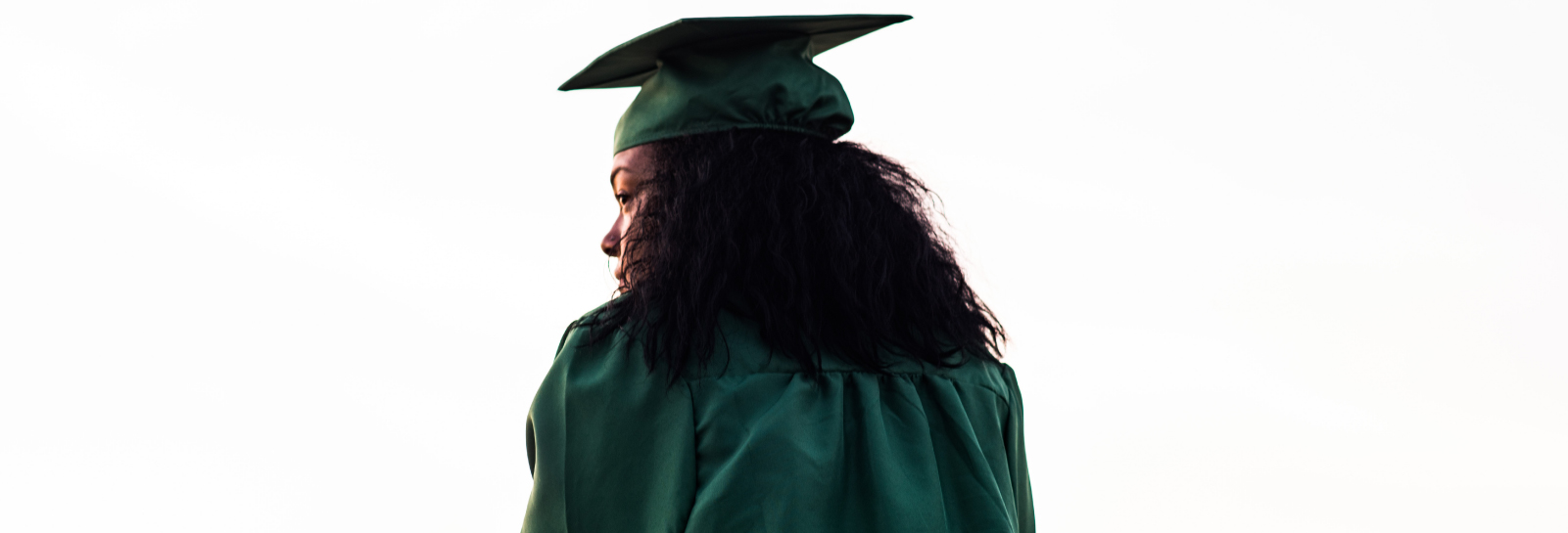 a behind shot of a woman in a graduation cap and gown