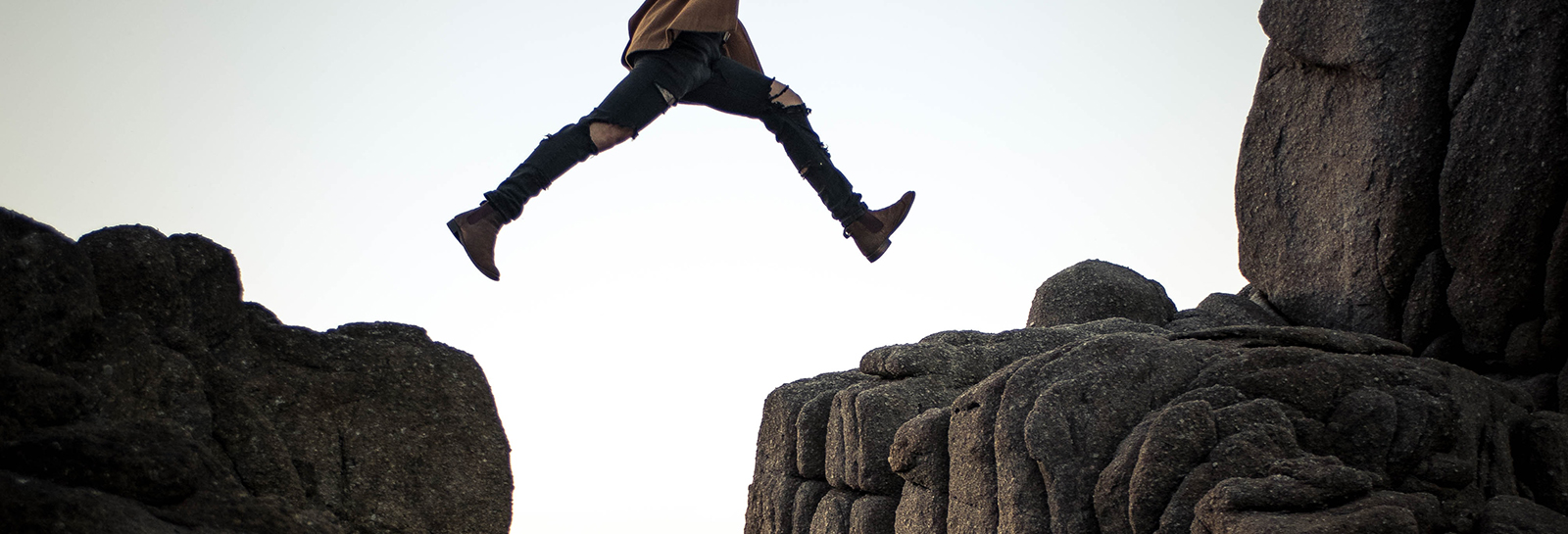 a person jumping over a small fissure