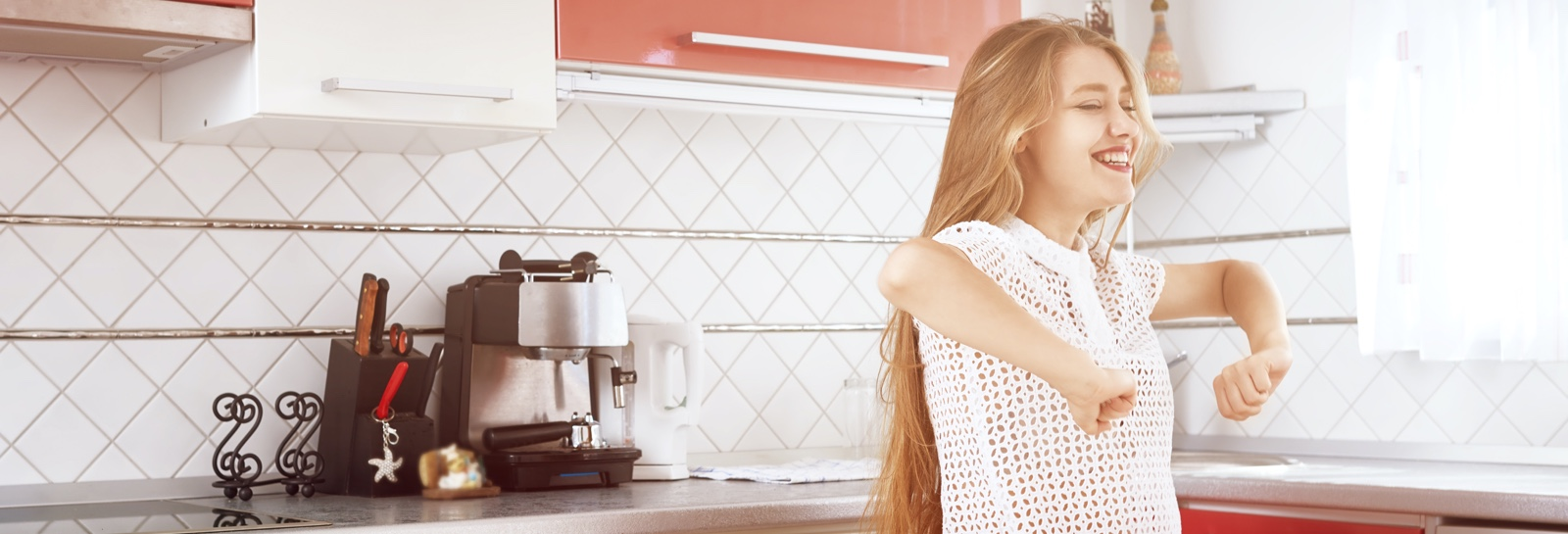 a woman smiling and dancing in the kitchen