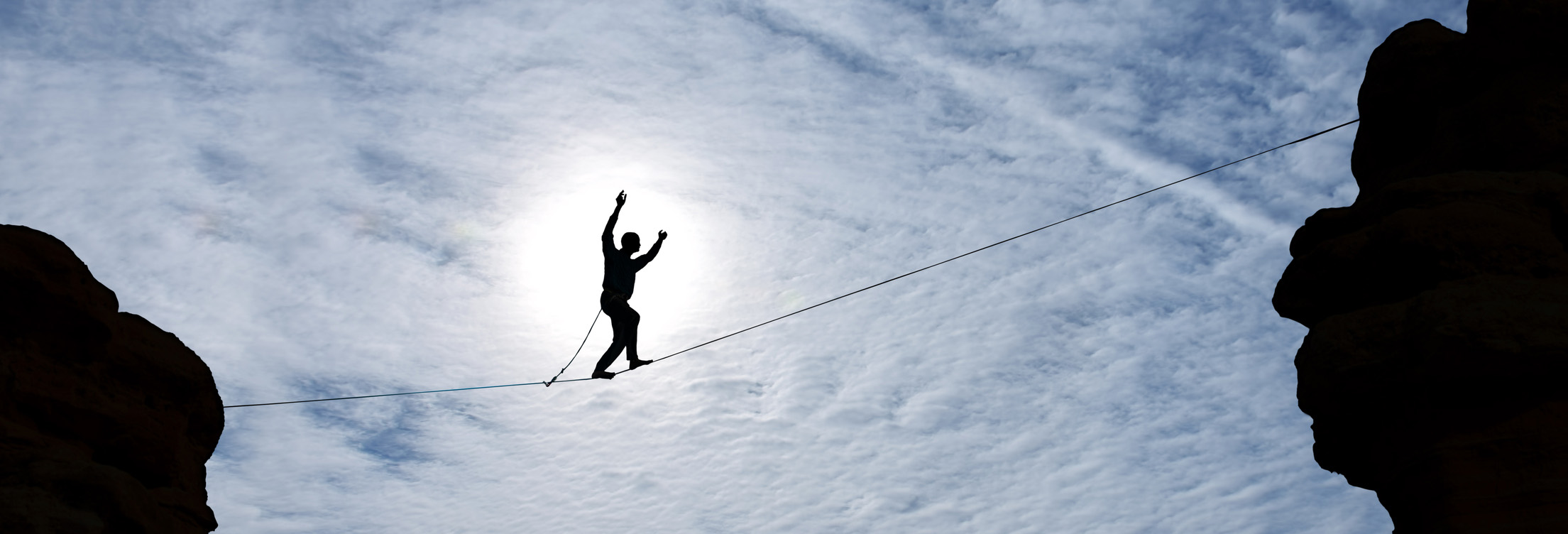 an upward shot of a person tight rope walking over a canyon