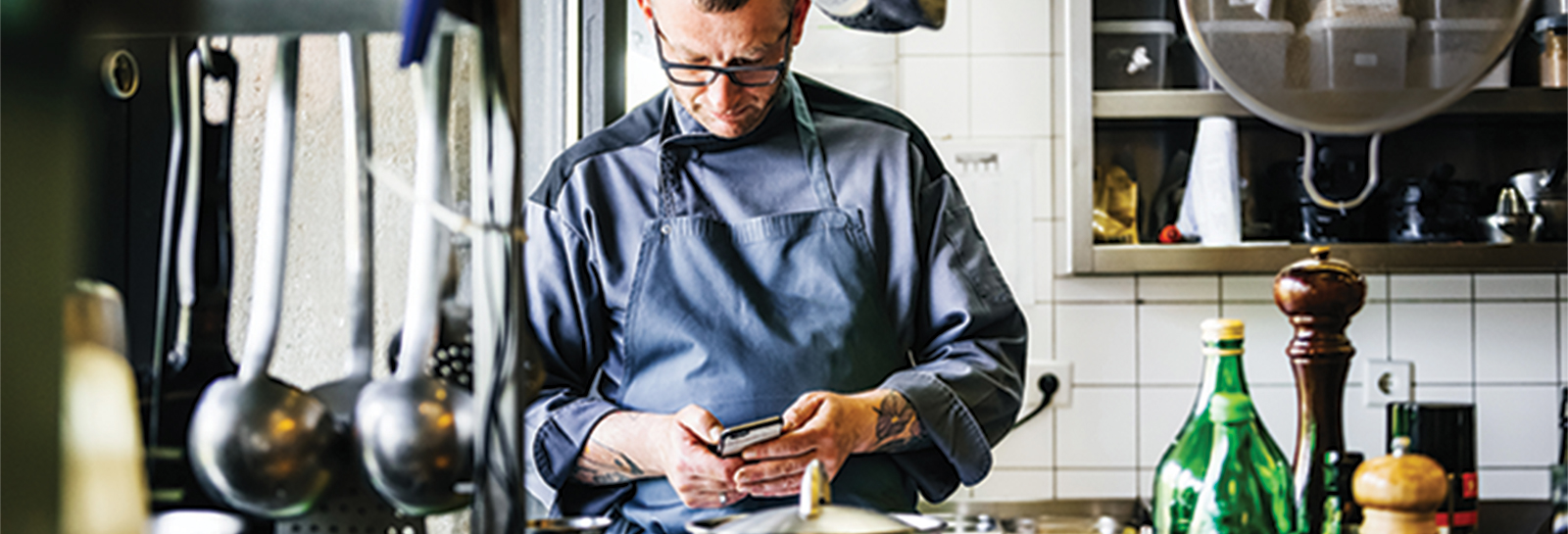 a chef texting on his phone in a kitchen