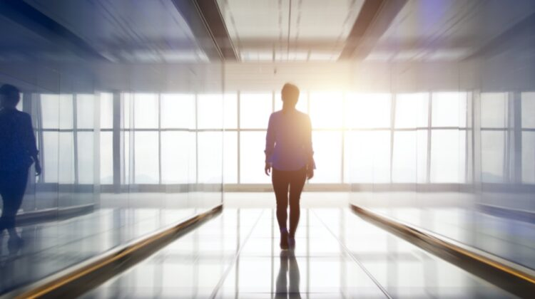 a person walking down a hallway, the sun is shining very brightly through the hallway