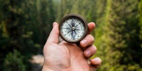 a person holding a compass in the wilderness