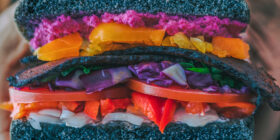 hands holding a sandwitch made with black bread and colorful fillings